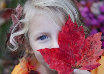 girl-peeking-out-from-behind-leaf